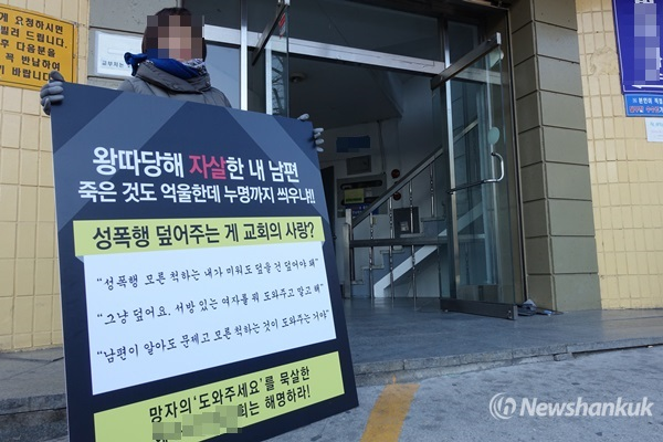 Mrs. A holds a placard demanding for the truth behind her husband's death during a protest in front of the Y Church, Songpa-gu, Seoul, March 13, 2015. (NewsHankuk DB)