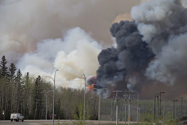 Thick clouds of black smoke from a wildfire in Fort McMurray, Alberta, Canada, billow into the sky on April 4 (local time). The Alberta government has declared a provincial state of emergency. (AP=Newsis)