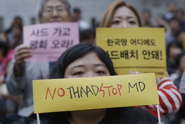 "A South Korean protester attends a rally to oppose a deployment of the Terminal High-Altitude Area Defense, or THAAD, in Seoul, South Korea, Saturday, Sept. 3, 2016. The advanced U.S. missile defense system will be deployed in a rural farming town in southeastern South Korea, Seoul officials announced on July 13, angering not only North Korea and China but also local residents who fear potential health hazards that they believe the U.S. system might cause. The signs read ""We oppose a deployment of the THAAD."" (AP Photo/Ahn Young-joon=newsis)"
