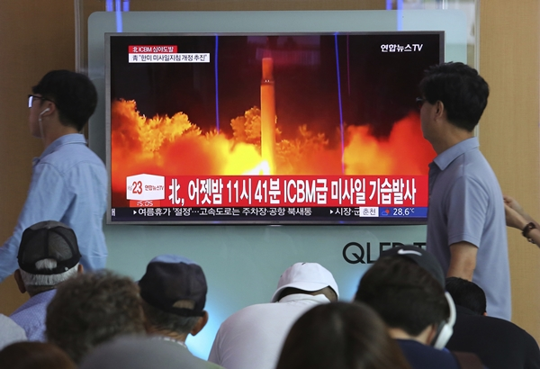 """People watch a TV news program showing an image of North Korea's latest test launch of an intercontinental ballistic missile (ICBM), at the Seoul Railway Station in Seoul, South Korea, Saturday, July 29, 2017. The clear message after Friday's late-night test, the second in a month of a missile that may be able to reach most of the U.S. mainland: Get used to this _ it's the new normal. The signs read """"North Korea launched an ICBM missile at 11:41 p.m. last night."""" (AP Photo/Ahn Young-joon=newsis)"""