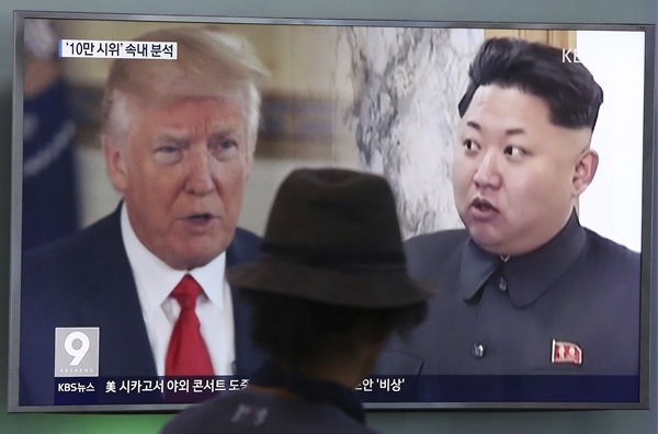 "FILE - In this Aug. 10, 2017, file photo, a man watches a television screen showing U.S. President Donald Trump and North Korean leader Kim Jong Un during a news program at the Seoul Train Station in Seoul, South Korea. Trump's recent invocation of ""fire and fury"" in response to North Korea's nuclear weapons program had a familiar ring to it. It's the kind of dramatic rhetoric that North Korea regularly uses in its public statements. (AP Photo/Ahn Young-joon, File=newsis)"