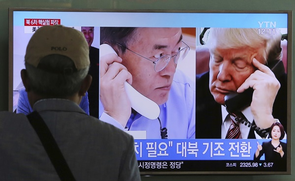 "A man watches a television screen showing U.S. President Donald Trump, right, and South Korean President Moon Jae-in during a news program at the Seoul Railway Station in Seoul, South Korea, Tuesday, Sept. 5, 2017. The signs read ""Need sanctions on North Korea.""(AP=Newsis)"