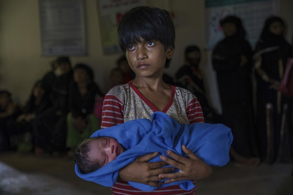 Rohingya Muslim girl Afeefa Bebi, who recently crossed over from Myanmar into Bangladesh, holds her few-hours-old brother as doctors check her mother Yasmeen Ara at a community hospital in Kutupalong refugee camp, Bangladesh, Wednesday, Sept. 13, 2017. The family crossed into Bangladesh on Sept. 3. Recent violence in Myanmar has driven hundreds of thousands of Rohingya Muslims to seek refuge across the border in Bangladesh. But Rohingya have been fleeing persecution in Buddhist-majority Myanmar for decades, and many who have made it to safety in other countries still face a precarious existence. (AP Photo/Dar Yasin=Newsis)