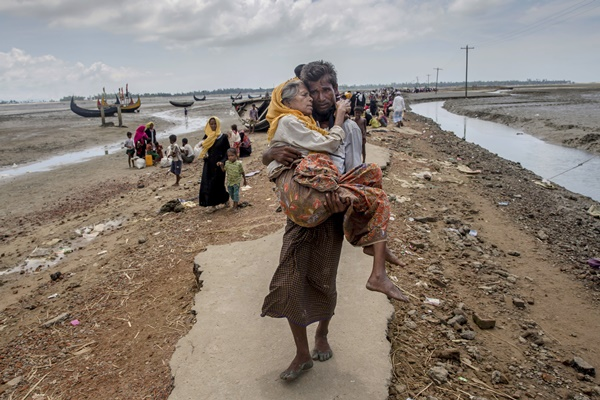 In this Sept. 16, 2017, file photo,  Abdul Kareem, a Rohingya Muslim man, carries his mother, Alima Khatoon, to a refugee camp after crossing over from Myanmar into Bangladesh, at Teknaf, Bangladesh. After a series of attacks by Muslim militants in August, security forces and allied mobs retaliated by burning down thousands of homes in the enclaves of the predominantly Buddhist nation where the Rohingya live. (AP Newsis)