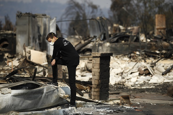 "Benjamin Lasker, 16, pauses while looking at what remains of his home after a wildfire swept through Sunday, Oct. 15, 2017, in Santa Rosa, Calif. With the winds dying down, fire officials said Sunday they have apparently ""turned a corner"" against the wildfires that have devastated California wine country and other parts of the state over the past week, and thousands of people got the all-clear to return home. (AP=Newsis)"