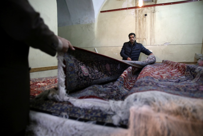 In this Monday, Dec. 10, 2018 photo, Iranian carpet seller Mahmoud Morshedi displays carpets at his shop at the grand bazaar in Kashan, Iran. Before the Trump administration withdrew from the nuclear deal with world powers and began restoring crippling sanctions earlier this year, the $425 million a year Persian carpet industry kept an ancient artistic tradition alive while providing much-needed income to Iranians as well as Afghan refugees, who create much of the more luxurious hand-woven pieces. (AP Photo/Vahid Salemi=Newsis)