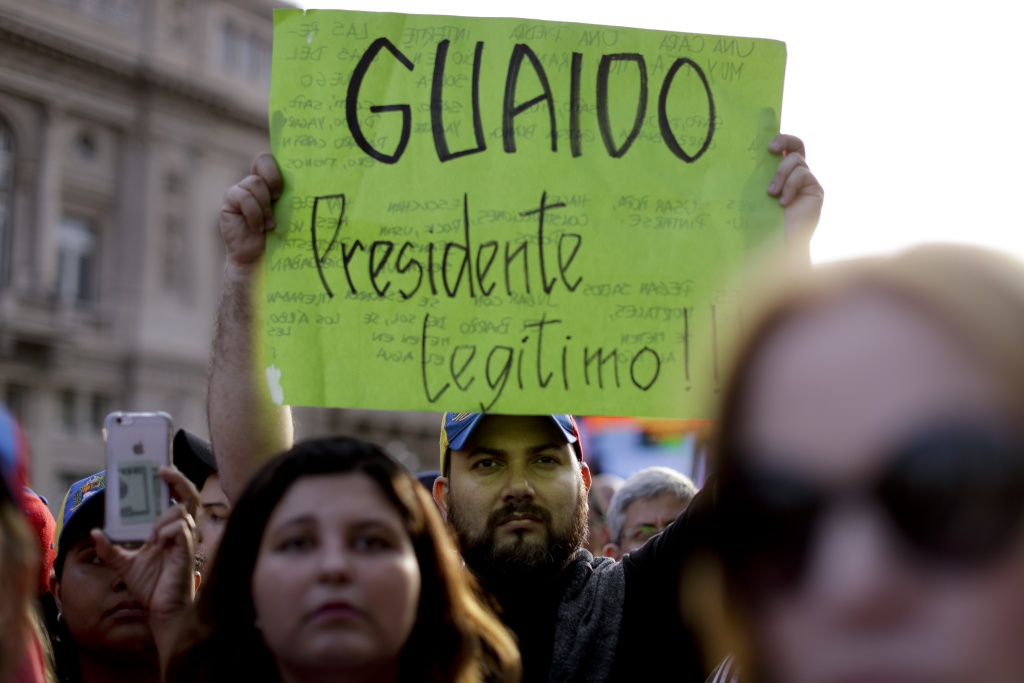 "A Venezuelan anti-government protester holds a sign that reads in Spanish ""Guaido legitimate President!"" during a demonstration in Buenos Aires, Argentina, Wednesday, Jan. 23, 2019. Hundreds of people, mostly Venezuelan migrants, held a rally against Venezuelan President Nicolas Maduro and in favor of Juan Guaido, head of Venezuela's opposition-run congress who today proclaimed himself president of the South American nation. (AP Photo/Natacha Pisarenko=Newsis)"