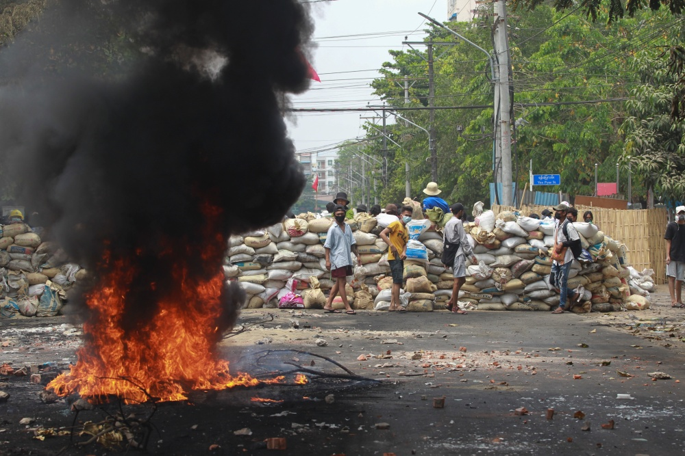 Anti-coup protesters stand beside a burning tire as they fortify their position against the military during a demonstration in Yangon, Myanmar on Tuesday March 30, 2021. Thailand's prime minister denied Tuesday that his country's security forces have sent villagers back to Myanmar who fled from military airstrikes and said his government is ready to shelter anyone who is escaping fighting.(AP Photo=Newsis)