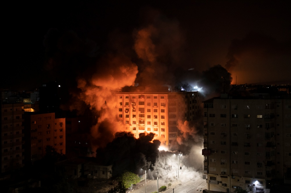 Smoke caused by Israeli airstrikes are seen at a residential building in Gaza City, early Wednesday, May 12, 2021. (AP Photo/Khalil Hamra=Newsis)